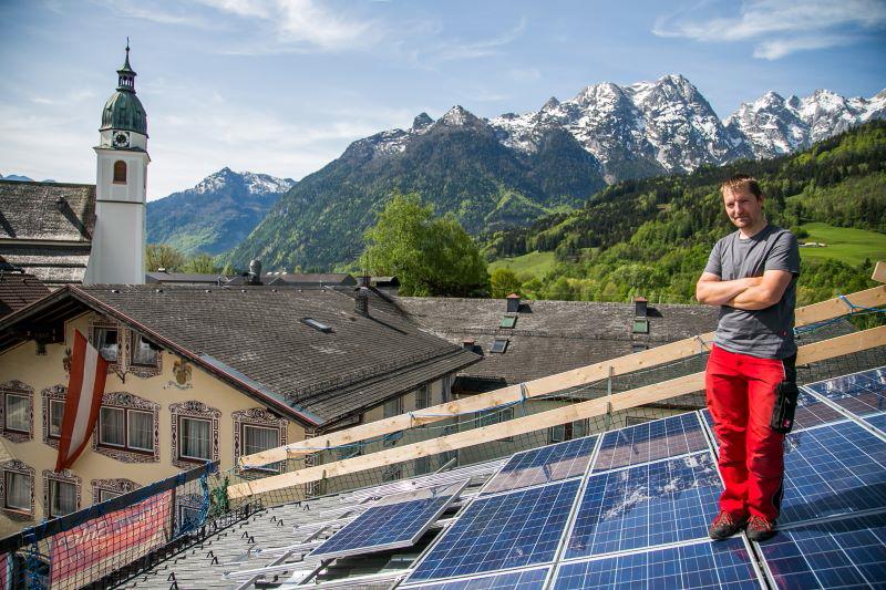 Eine PV-Dachanlage mit Monteur in einem Dorf vor dem Hintergrund schneebedeckter Alpen.