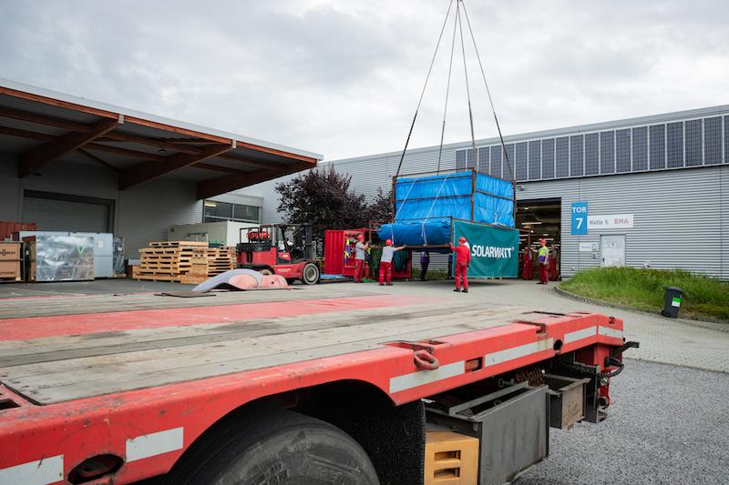 Container mit Laminatoren werden mit Kran in Modulproduktion von Solarwatt gebracht