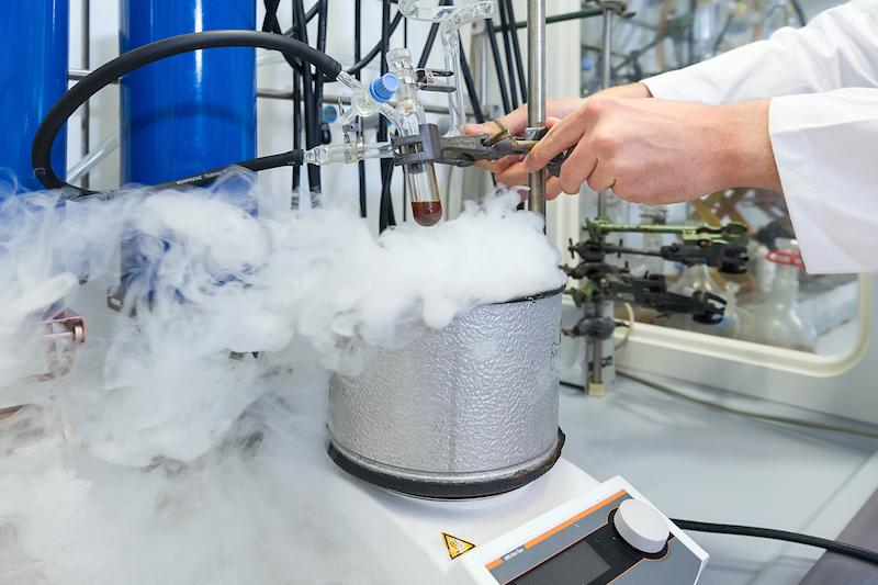 Im chemischen Labor steht ein dampfender Topf auf einem Kochfeld. Ein wissenschaftler experimentiert mit einer dunklen Flüssigkeit in einem Reagenzglas.