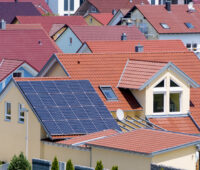 Viele Dächer von Ein- und Zweifamilienhäusern, davon im Vordergrund ein Dach mit einer blauen Photovoltaikanlage