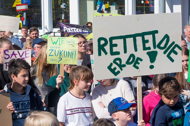 """Schüler zeigen auf Klimademo selbstgebastelte Transparente. Ganz vor ein Plakat """"Rettet die Erde!"""""""