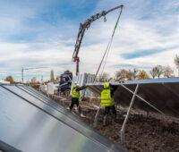 Solarthermie: Bauarbeiter bugsieren einen Großkollektor, der an einem Kran hängt, in seine Halterung