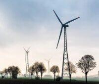 Windenergieanlagen auf Gittermasten im Gegenlicht