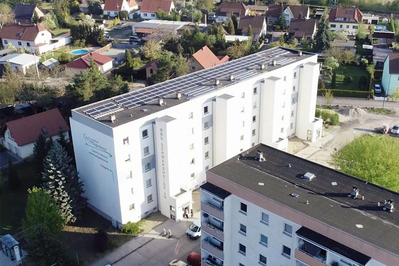 Luftbild einer Photovoltaikanlage auf dem Dach eines Wohnblocks