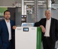 Das Bild zeigt in der Mitte eine neue Pelletheizung von Ökofen, links davon ÖkoFEN-Geschäftsführer Stefan Ortner und rechts Firmengründer Herbert Ortner