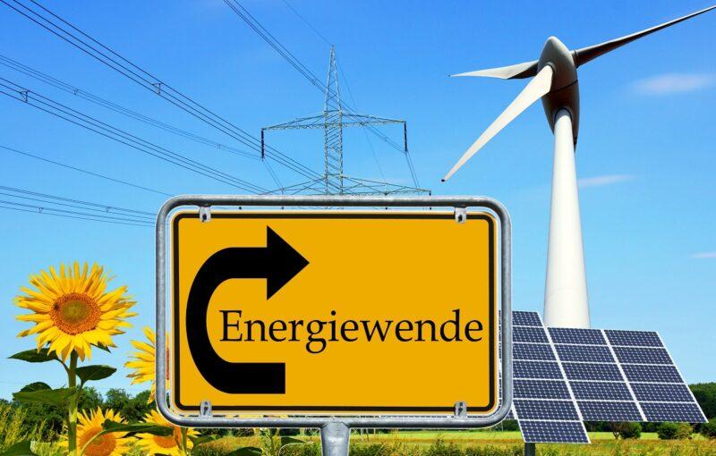 Ein animiertes Bild zeigt ein Verkehrsschild, das auf die Energiewende zeigt udn im Hintergrund Wind, Solarenergie udn Strommasten.