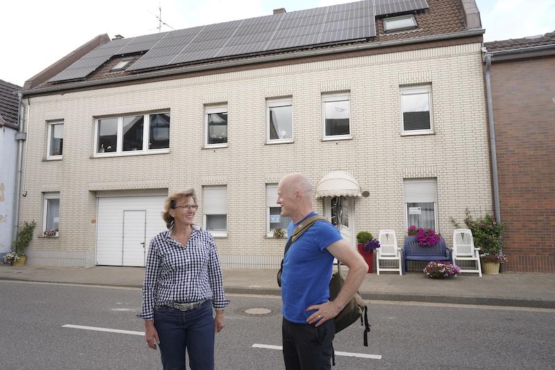 Eine Frau und ein Mann vor einem Haus mit Photovoltaik-Anlage, in Keyenberg.