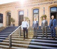 Vier Männer auf Treppe vor Backstein-Gebäude