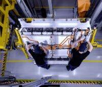 Batterie-Produktion bei Mercedes-Benz: Zwei Männer arbeiten an einem Schaltschrank.