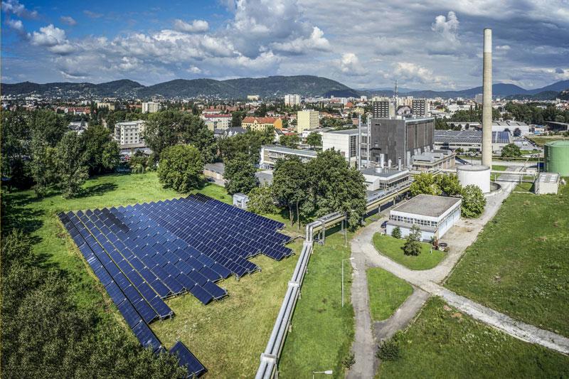 Luftbild der Solarthermieanlage am Heizwerk in Graz vor Stadtkulisse