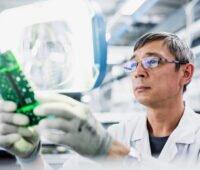 Mann mit Brille hält eine Solarelektronik-Platine in den behandschuhten Händen