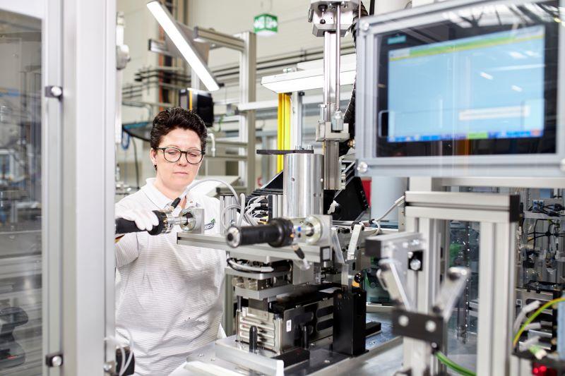 Eine Arbeiterin hantiert an Maschinen in einer Batteriefabrik.