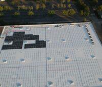 Zu sehen ist ein Luftbild einer beginnenden PV-Montage von Adler Smart Solutions auf einem großen Flachdach.