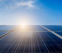 Solarmodule vor blauem Himmel und der Sonne.