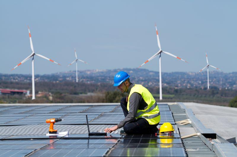 Ein Handwerker montiert Solarmodule auf einem Flachdach. Im Hintergrund drehen sich SWindräder.