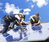 Monteure mit guter Laune installieren eine PV-Anlage.