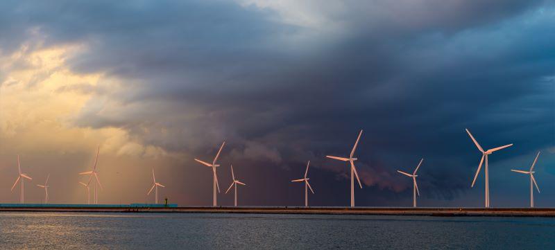 Windkraftanlagen am Meer vor dunklen Wolken.