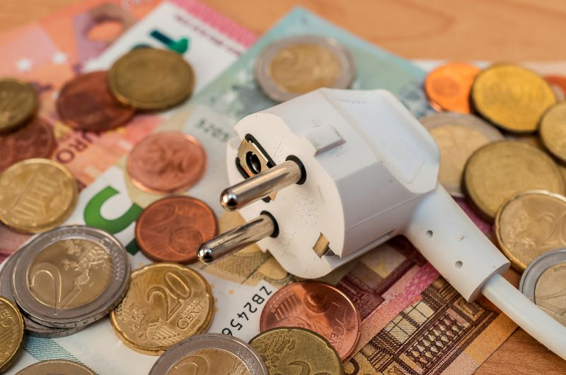 Symbolbild mit Euroscheinen- und münzen sowie einem Stecker.