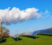 Rechts und im Vordergrund Photovoltaik-Module auf einer grünen Wiese, im Hintergrund Windkraftanlagen, links ein fossiles Kraftwerk - Energiewende ist Wahlkampf-Thema