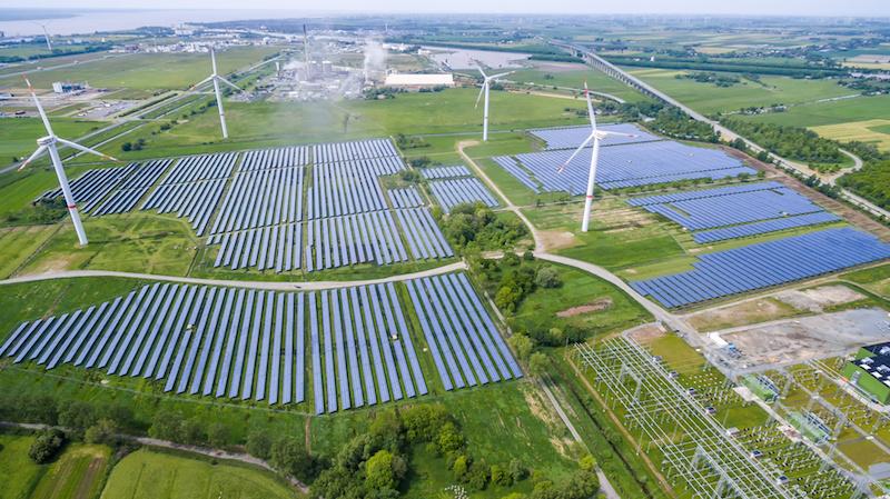 Im Vordergrund eine Photovoltaik-Freiflächenanlage mit Windkraftwerken, im Hintergrund ein Dorf.