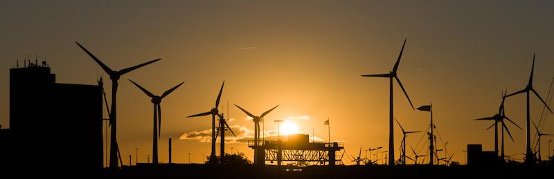 Bei untergehender Sonne Windkraftanlagen mit Industrieanlagen