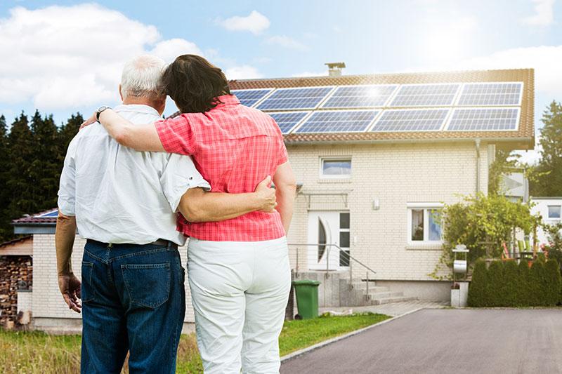 Vorn ein älteres Paar, im Hintergrund ein Einfamilienhaus mit einer Photovoltaik-Anlage auf dem Dach