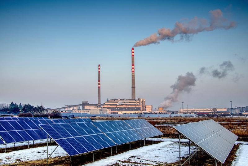 Photovoltaikanlage vor Kohlekraftwerk mit rauchenden Schloten