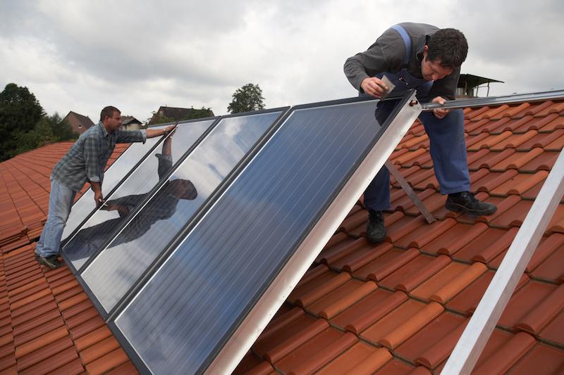 Zwei Installateure montieren Solarkollektoren auf einem Dach.