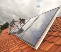 Solarthermie-Module aufgeständert auf einem Ziegeldach mit Handwerkern im Hintergrund vor einem wolkenverhangenen Himmel