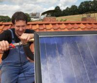 Installateur montiert Solarthermie-Anlage