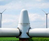 Rotorkopf einer Windkraftanlage abgebaut auf dem Rasen liegend, im Hintergrund zwei Windkraftanlagen in Betrieb