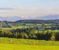 Bayerische bäuerliche Landwirtschaft, im Hintergrund die Alpen, rechts davor, kaum zu erkennen, ein Windpark
