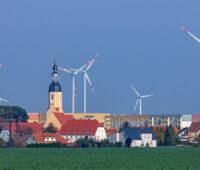Ortsansicht mit Windkraftanlagen im Hintergrund