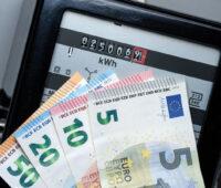 Im Hintergrund ein Stromzähler, im Vordergrund Geldscheine