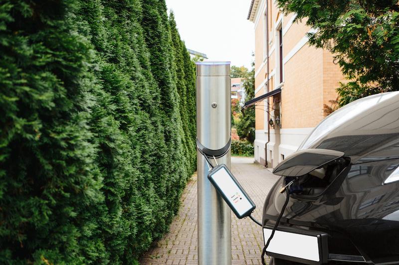 Ladesäule für ein Elektroauto neben einem Busch, im Hintergrund ein Haus. Angeschlossen ist ein Fahrzeug.