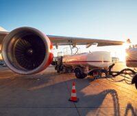 Blick auf Flugzeug von hinten mit daneben stehendem Tankwagen. Symbolbild für grüne Flugzeugkraftstoffe, SAF, E-Fuels.