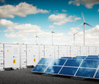 Container zur Wasserstoffspeicherung, rechts daneben Photovoltaikanlagen, im Hintergrund Windkraftanlagen