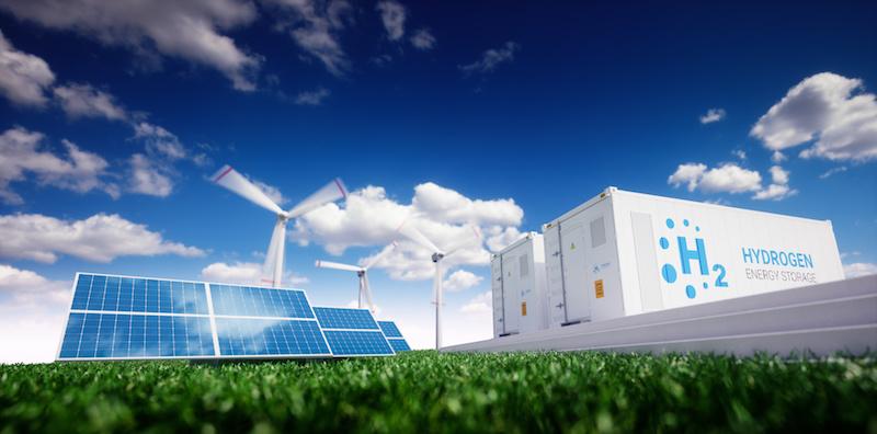 Auf einer grünen Wiese stehen links Solarmodule, im Hintergrund Windkraftanlagen, rechts Container mit der Aufschrift H2 - Hydrogen (Wasserstoff)