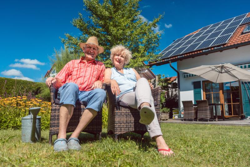 EIn älteres Paar im Garten, rechts im Hintergrund ein Haus mit Solarstromanlage.