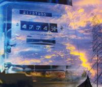 Auf der Glasabdeckung eines analogen Stromzählers spiegeln sich ein Strommast und Stromleitungen sowie Wolken.