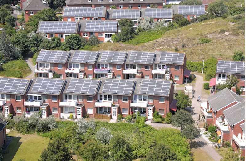 Eine Gebäudesiedlung mit Solarmodulen auf den Dächern.