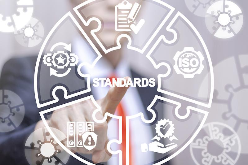 Grafik zu Standardisierung im Vordergrund - darauf zeigt ein Mann im Anzug mit seinem Finger. Visualisierung von Normungsgremien