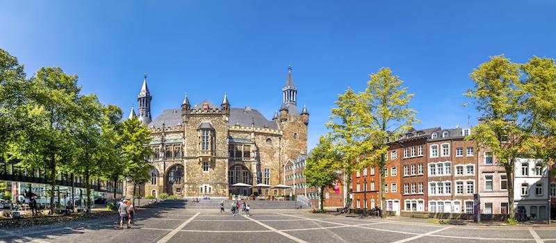 Das Rathaus von Aachen im Hintergrund, vorn ein Platz mit Gebäuden und Bäumen am Rand.