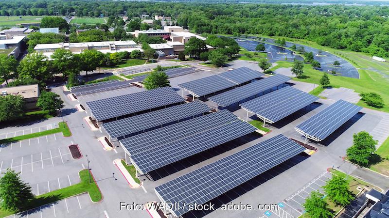 Blick von oben auf Solar-Parkplätze, an die Fläche grenzt rechts Wald, im Hintergrund Gebäude