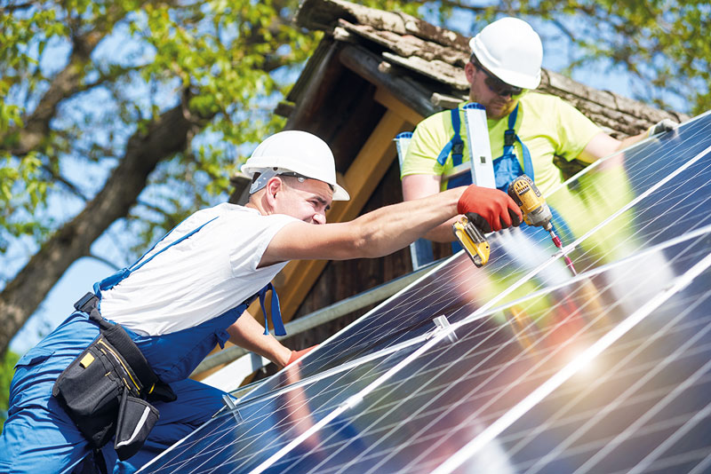 Monteure befestigen Photovoltaikmodule auf einem Schrägdach