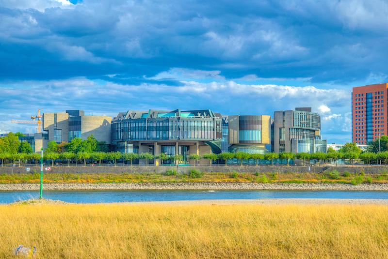Landtagsgebäude von NRW in Düsseldorf von der anderen Rheinseite aus betrachtet mit dunklen Wolken über dem Gebäude