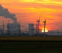 Vor einem orangen Abendhimmel mit untergehender Sonne sind die Kühltürme eines Koihelkraftwerks zu sehen, davor Strommasten und Windkraftanlagen.
