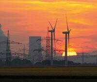 Energiewende. Windkraftanlagen vor Kohlekraftwerk und Strommasten. Ganz im Hintergrund die untergehende Sonne.