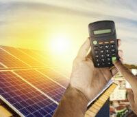 Taschenrechner wird von Händen hochgehalten. Im Hintergrund eine Photovoltaikanlage auf einem Dach.