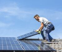 Installateure auf einem Dach montieren oder demontieren PV-Module